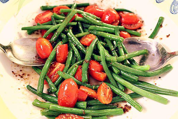 Bohnen und Tomaten in Vinaigretten wenden